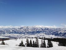 Spring mountains. View from a ski slope showing the mountains, the clear blue sky and the rice fields peeking out from below the layers of snow royalty free stock photos