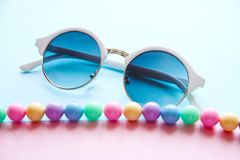 Spring multi-colored beads and round white glasses royalty free stock image