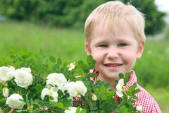 Spring in the nature and spring in the soul. Happy boy smiles near the flowers Royalty Free Stock Image