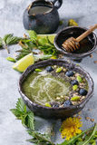 Spring nettle and dandelion smoothie. Spring green nettle and dandelion smoothie bowl served with lime, yellow flowers, young leaves, oat flakes, chia seeds royalty free stock images