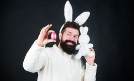 Spring, new life and fertility. Bearded man in rabbit costume with easter egg and hare toy. Spring holiday. Happy man. With rabbit ears holding bunny toy and stock photo
