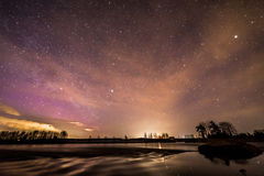 Spring night by the river. Beautiful spring night and starlit sky by the river. Fascinating colors appeared in the sky Royalty Free Stock Photos