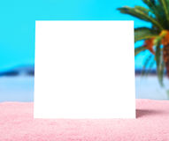 Spring offer or summer sale template background. White blank square card with free copy space on a towel on beach. Spring offer or summer sale template stock photo