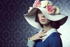 Spring old-style girl with hat. Elegant pretty woman in blue dress with a spring white hat , with pink and white roses over Royalty Free Stock Photos