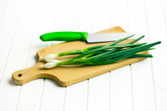 Spring onion on cutting board Royalty Free Stock Photos