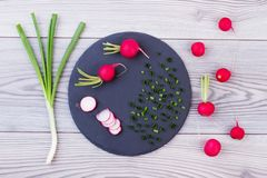 Spring onion and radishes on slate board. Top view on red radishes and green organic onion on wooden background. Food for vegans Stock Photography