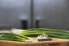 Spring Onions And Knife On Chopping Board Stock Images