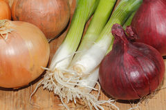 Spring onions, onions, vegetables, wooden board. Spring onions, onions, vegetables on a wooden chopping board Royalty Free Stock Photos
