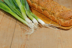 Spring onions, onions, vegetables. On a wooden chopping board Stock Photos