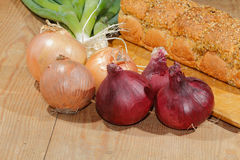 Spring onions, onions, vegetables. On a wooden chopping board Stock Photo