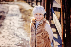 Spring outdoor portrait of happy child girl in faux fur coat Stock Image
