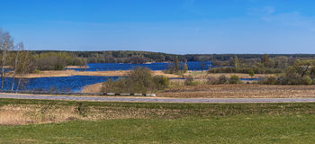 Spring panorama with the blue lake, island, sky and forest on th royalty free stock image