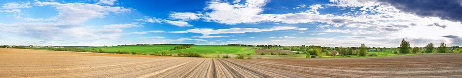 Spring panorama of landscape with ploughed field. Hills, blue sky with white clouds. panoramic view Stock Image