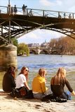 Spring in Paris Seine riverbanks near Pont des Arts friendship group royalty free stock image