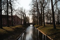 Spring park with a canal and a bridge in the background royalty free stock images