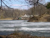Spring park view with water. Ice melting on the pond in spring park Royalty Free Stock Photo