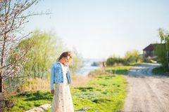 Spring photo of a beautiful young woman on a background of nature. Girl in a light dress and a denim jacket in spring with bloomin stock photos