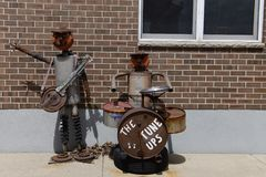 The Tune Ups. This is a Spring picture of a piece of public art titled: The Tune UPS, on display in front of a automotive repair shop in Elizabeth, Illinois in Royalty Free Stock Image