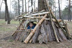 In the spring in a pine forest, the boy built a hut of sticks. Stock Image