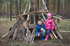 In the spring in a pine forest, a brother with a small sister bu Stock Images