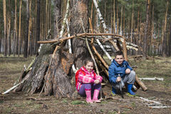 In the spring in a pine forest, a brother with a small sister bu Stock Photos