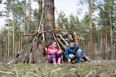 In the spring in a pine forest, a brother with a small sister bu Royalty Free Stock Photos