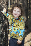Spring in a pine forest is a little funny girl. Stock Photos