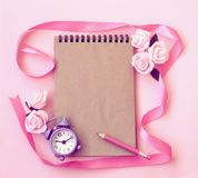 Spring pink background with alarm clock, rose flowers, pencil, n stock photo