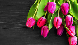 Spring pink tulips bouquet over wooden background Stock Photos