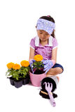 Spring Planting. A young Asian girl plants a Marigold in a pot Royalty Free Stock Photography