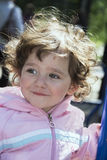In the spring on the playground playing little curly girl. Stock Photography