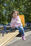 In the spring on the playground playing little curly girl. Royalty Free Stock Photos
