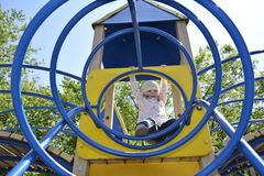 In the spring on the playground playing little girl. Stock Photography