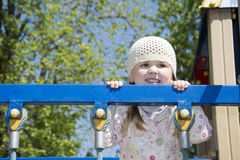 In the spring on the playground playing little girl. Stock Images
