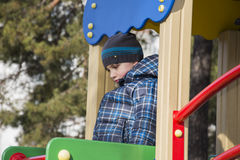 In the spring of the playground is a sad hurt the boy. Stock Photos