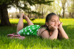 Spring Portrait. A young girl laying in the grass relaxing and enjoying the spring weather Royalty Free Stock Images