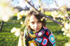 Woman in spring. Young woman wearing a colorful scarf, standing behind blossomed tree branches in spring Stock Photos