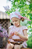 Spring portrait of adorable child girl in pink dress making lilac wreath in sunny garden Royalty Free Stock Images
