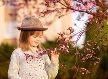 Spring portrait, adorable little girl in hat walk in blossom tree garden on sunset. Spring portrait, adorable little girl in hat walk in blossom tree garden royalty free stock photos