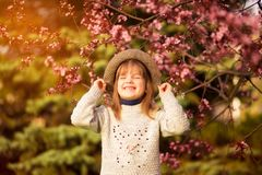 Spring portrait, adorable little girl in hat walk in blossom tree garden on sunset. Spring portrait, adorable little girl in hat walk in blossom tree garden royalty free stock photo