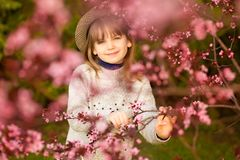 Spring portrait, adorable little girl in hat walk in blossom tree garden. On sunset royalty free stock image