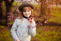 Spring portrait, adorable little girl in hat walk in blossom tree garden on sunset. Spring portrait, adorable little girl in hat walk in blossom tree garden royalty free stock photography
