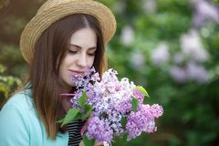 Spring portrait of a beautiful woman outdoors in the park, among the bushes blooming lilac. Young beautiful woman enjoying the smell of blooming lilac on a sunny stock image