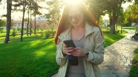Spring portrait of beautiful young redhair woman with funny sunglasses standing in park backlit and texting on stock video