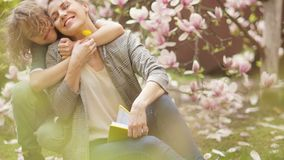 Spring portrait of a beautiful young woman with her son on a background of blooming magnolia. Mother`s day, spring stock footage