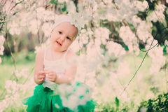 Spring portrait of cute baby girl in green skirt enjoying outdoor walk in blooming garden Stock Image