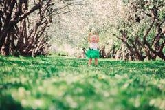 Spring portrait of cute baby girl in green skirt enjoying outdoor walk in blooming garden. Spring portrait of cute baby girl in green skirt enjoying outdoor walk Stock Images