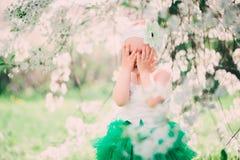 Spring portrait of cute baby girl in green skirt enjoying outdoor walk in blooming garden Stock Photography