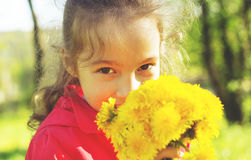 Spring portrait of cute little girl outdoors with dandelions. Stock Photo