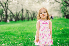 Spring portrait of cute little toddler girl in blue jeans dress walking in blooming park Stock Photo
